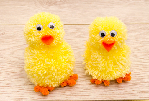 Making Easter Pom Pom Chicks using a pom pom maker and wool. You need yellow wool, two different sized pom pom makers, orange pipe cleaners for the feet, and orange felt for the beak plus stick on eyes.