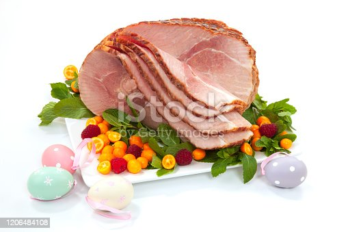 Closeup of delicious roasted sliced Easter ham with fresh mint, kumquat, and raspberries over white background. Easter eggs.