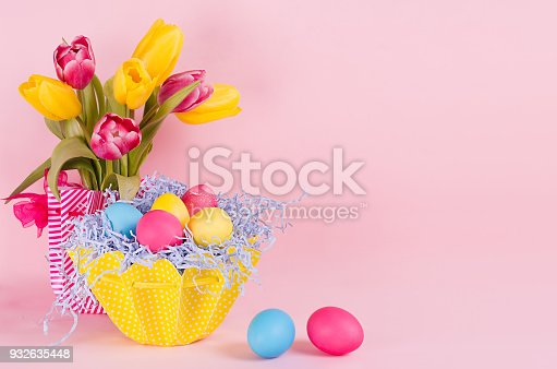 istock Easter spring home decor of yellow tulips, painted eggs, two eggs on pastel soft pink background. 932635448