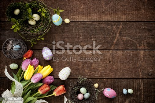 Easter Spring Tulips and a Basket of Easter Eggs on a Rustic Old Wood Background with Copy Space