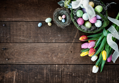 Easter Spring Tulips and a Basket of Easter Eggs on an old Wood Background