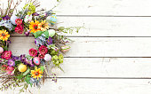 Easter spring flower wreath and Easter eggs on an old rustic white wood background