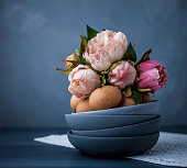 Easter still life arrangement with natural eggs and peony bouquet