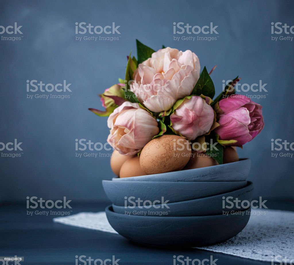 Easter still life arrangement with natural eggs and peony bouquet stock photo