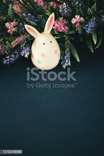Dark blue Easter still life background with Easter egg bunny and flowers