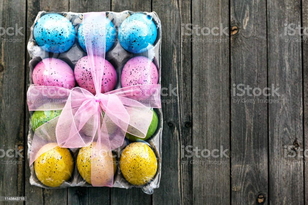 Easter still life with traditional decorative eggs colored in green, yellow, blue and pink on wooden background stock photo