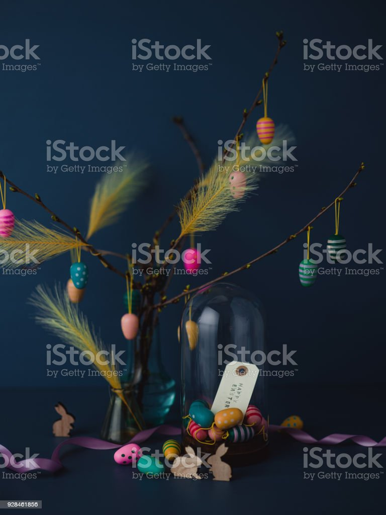 Easter still life with twigs and egg decorations with cruelty free artificial feathers on dark blue stock photo