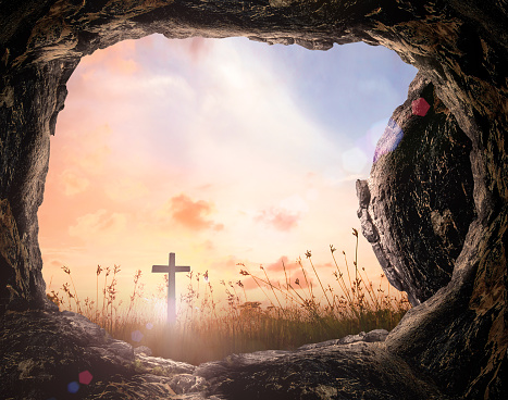 Tomb empty with cross at sunrise