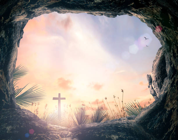 Easter Sunday concept Silhouette cross and empty tomb stone with palm leaves over meadow sunset background tomb stock pictures, royalty-free photos & images