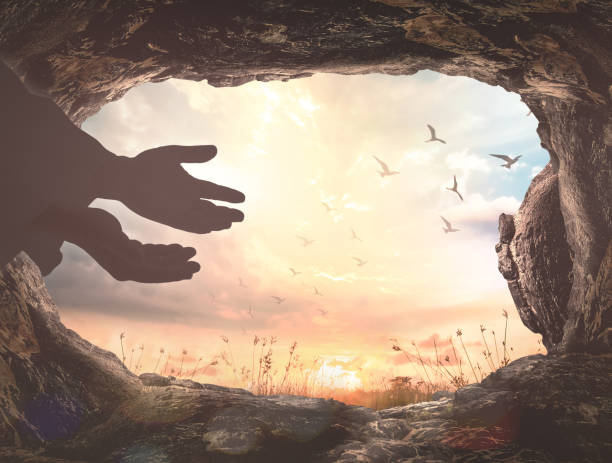 Easter Sunday concept Silhouette Jesus Christ hands with empty tomb stone and birds flying over meadow sunset background tomb stock pictures, royalty-free photos & images