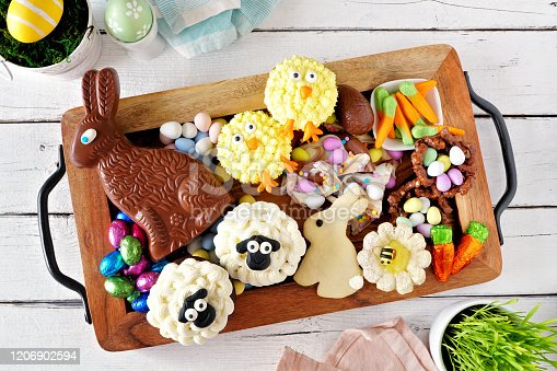 istock Easter sweets tray with an assortment of desserts and candy, top view over a white wood background 1206902594