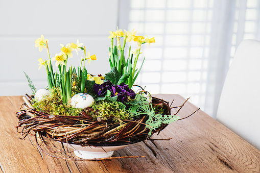 Easter table centerpiece decoration with daffodils and easter eggs