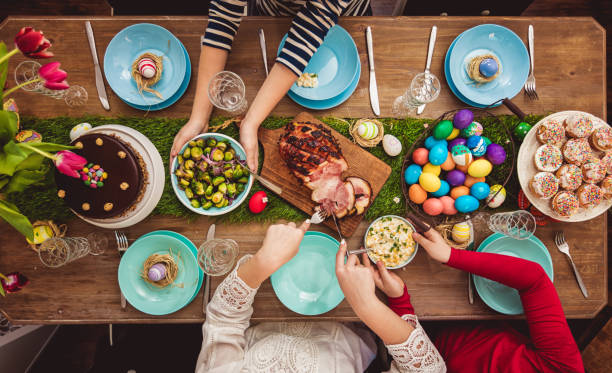 Easter Table Overhead view on decorated Easter table with family around easter stock pictures, royalty-free photos & images