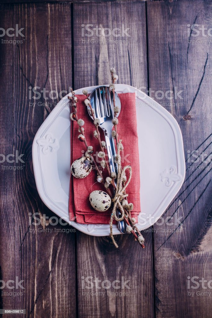 White or beige plate, cutlery, eggs and pussy willow on