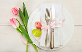 Easter table setting with pink tulips on white wooden background. Top view