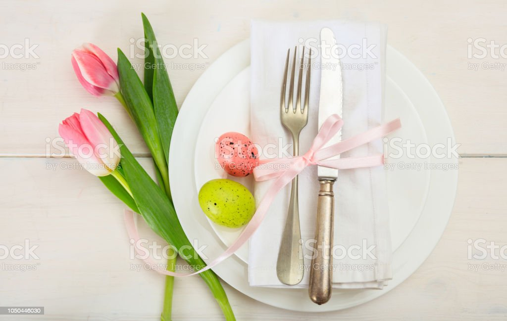 Easter table setting with pink tulips on white wooden background. Top view stock photo