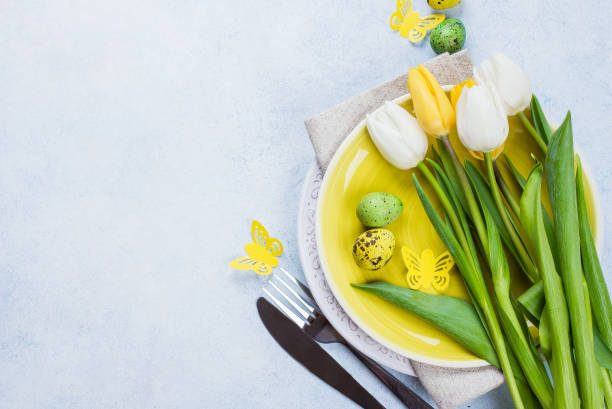 easter table setting with spring tulips, quail eggs and cutlery. spring holidays stone blue background. top view, flat lay, copy space - easter brunch stock photos and pictures