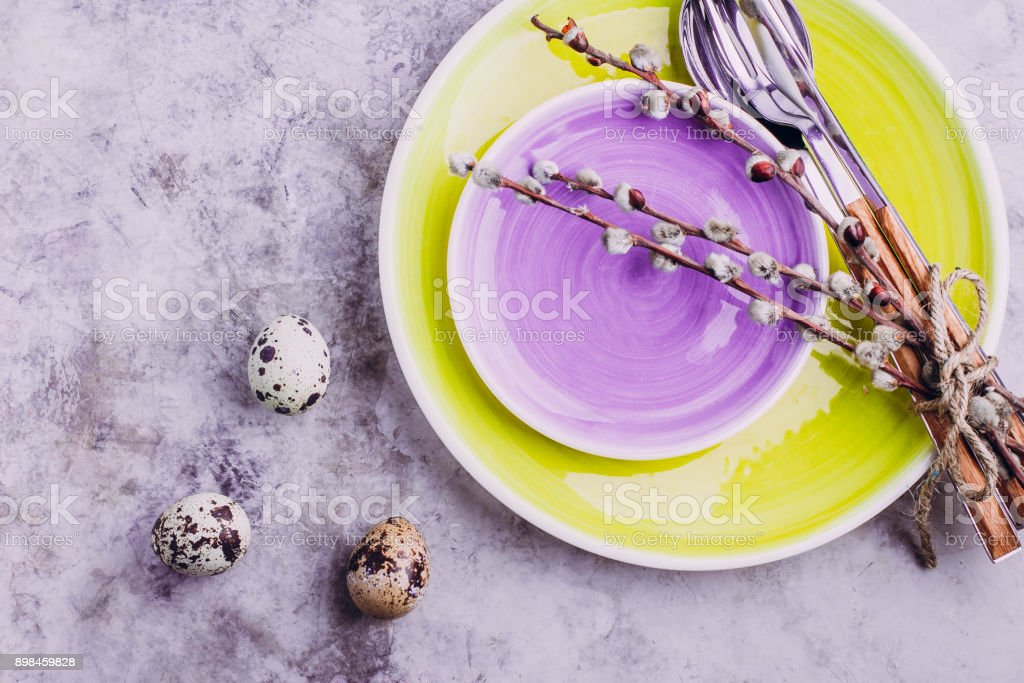 Yellow and purple plate, cutlery, quail eggs and pussy willow