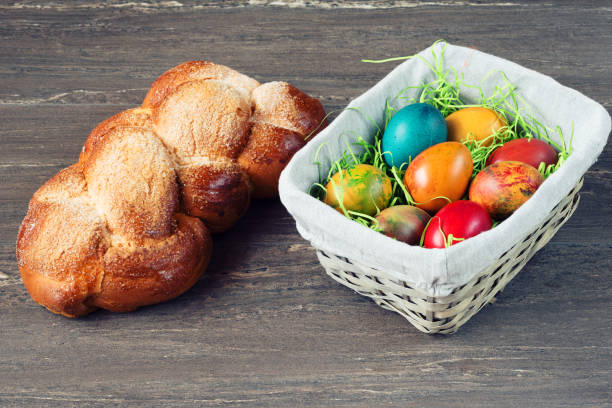 Easter wicker basket with colored eggs and Easter bread on grey wooden board. stock photo