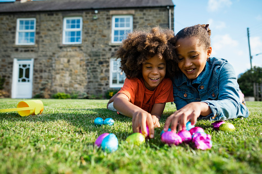 A front-view shot of a young boy with an afro and his older sister, they are lying down on their front smiling while holding their Easter eggs.