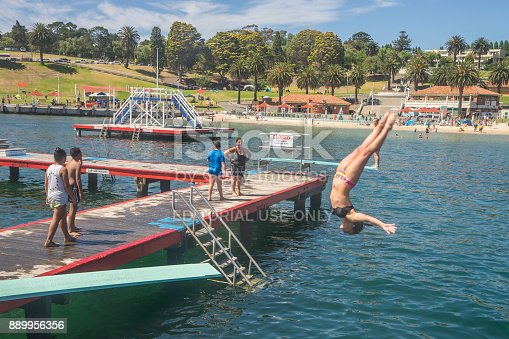 Geelong, Australia - February 4, 2017: A girl does a backflip from a diving board at the Eastern Beach Swimming Enclosure.