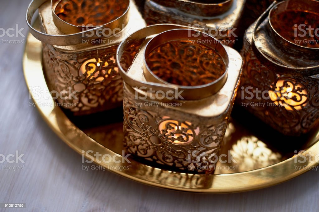 Eastern candlesticks with patterns in gold leaf with a burning candle.stand on a tray stock photo
