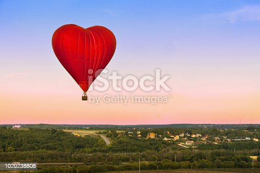 844061492 istock photo Eastern Europe: Lifestyle. Heart flying red hot air balloon in sunset blue pink sky with a copy space. 1020238808