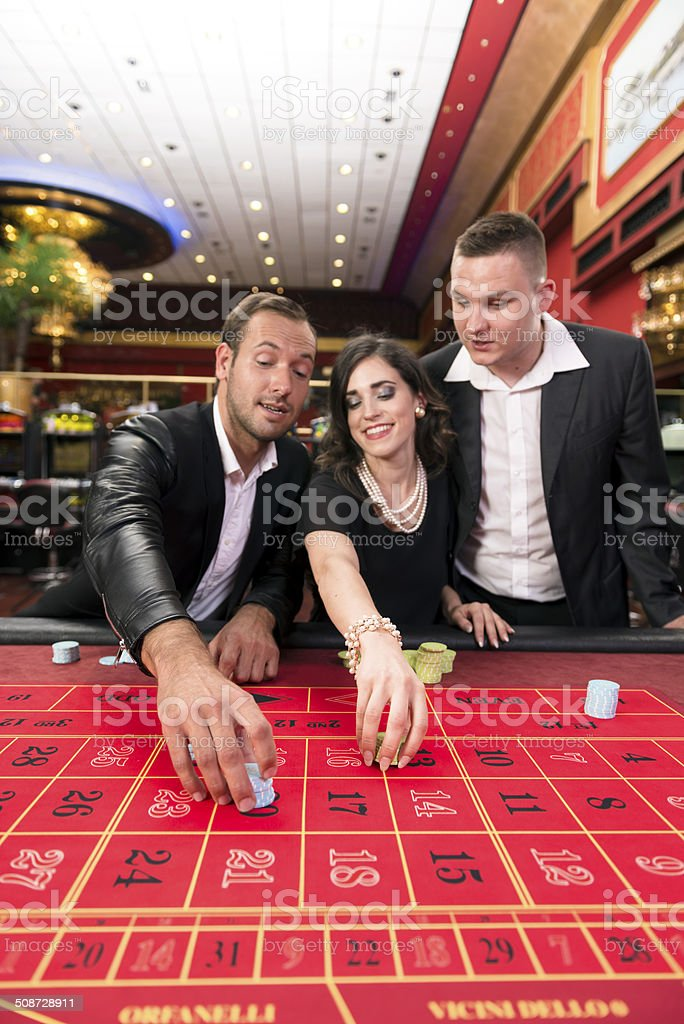 A group of friends playing on a roulette table in a casino,...