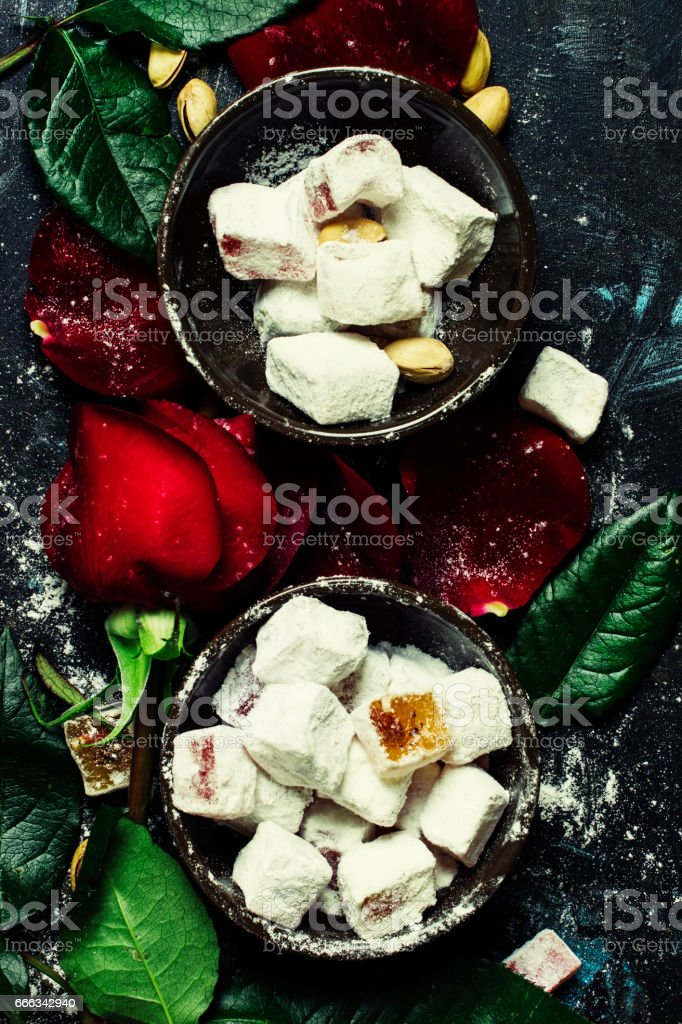 Eastern sweets with sugar powder, pistachios and rose petals stock photo