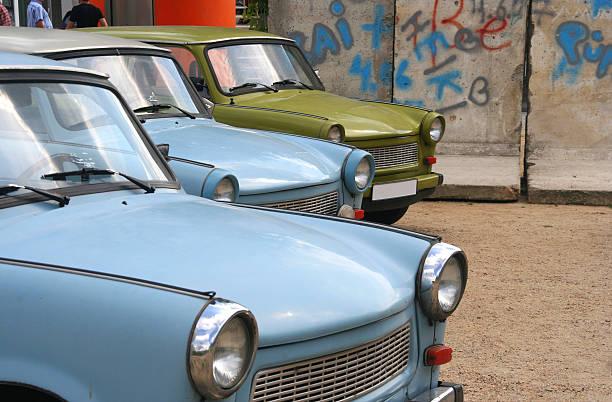 east-german cars at the berlin wall - oost duitsland stockfoto's en -beelden