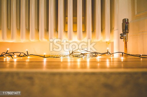 Quick, simple and cosy Christmas / New Year decoration: string of LED lights on wooden floor around column radiator.
