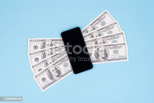 istock Easy and quick money send concept. Top above flat lay close up view photo of smart phone with money wings isolated pastel color blue background 1206898046