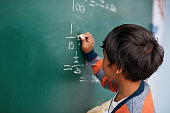 Cropped shot of a focussed young elementary school kid writing answers to math questions on a green chalkboard in the classroom