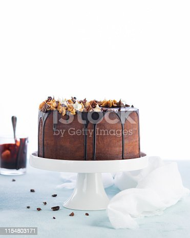 istock Easy Birthday Drip Cake with melted chocolate ganache with party decor on a white background. Copy space. Celebration concept. Trendy Cake. 1154803171