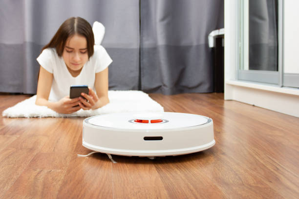 Easy cleaning.Young European girl resting with smartphone while robot vacuum cleaner collects dust stock photo