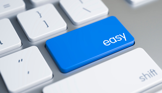 Easy Written on Blue Key of Metallic Keyboard. High Quality Render of a Modern Keyboard Button. The Button is Blue in Color and there is Caption Easy on It. 3D Render.
