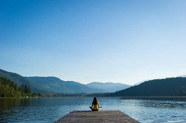 Easy Pose Tranquil Lakeside meditation at sunrise Female meditating doing sukhasana or Easy Pose during a yoga working at a pristine mountain lake tranquil scene stock pictures, royalty-free photos & images