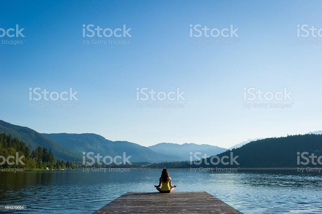 Fácil postura de meditación al atardecer apacible a orillas del lago - foto de stock