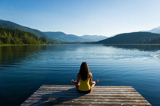 un cadre paisible en bord de lac, posture de méditation au lever du soleil - paysage zen photos et images de collection