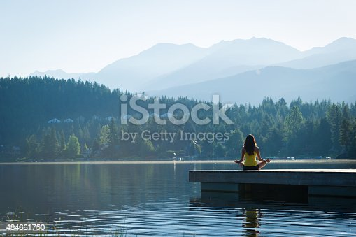Female meditating doing sukhasana or Easy Pose during a yoga working at a pristine mountain lake