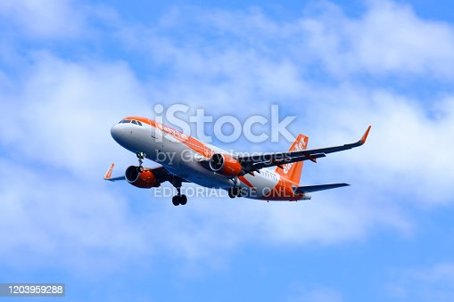 Easyjet Airbus A320 Airplane landing at Airport Cristiano Ronaldo on the Island Madeira, Portugal during a beautiful summer day with the Atlantic Ocean in the background.