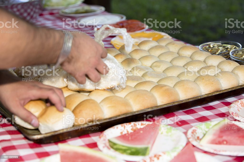 Eat and Drink: Person preparing dinner rolls for outdoor buffet stock photo