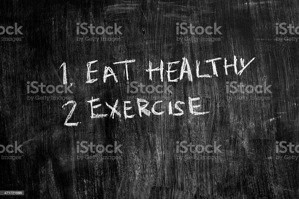 Eat healthy and exercise written on blackboard royalty-free stock photo