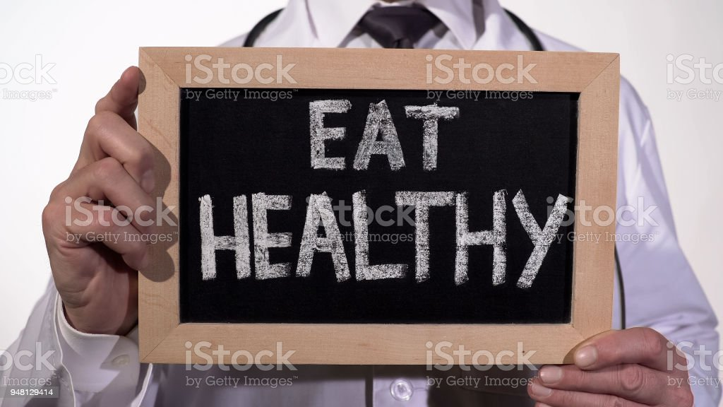 Eat healthy diet recommendation written on blackboard in nutrition doctor hands stock photo