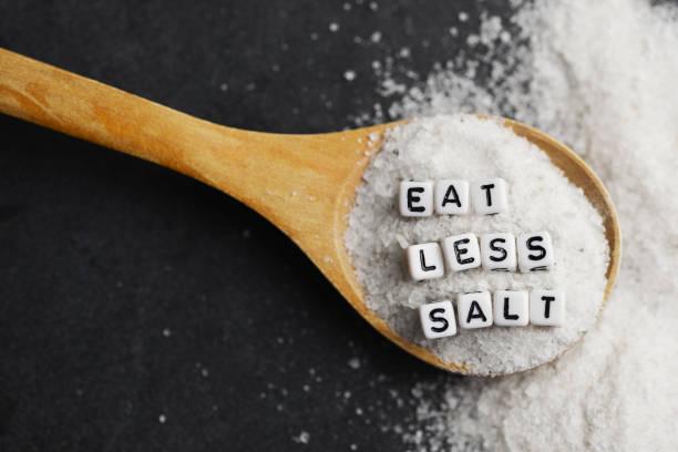 comer menos sal consejo escrito con perlas de plástico carta sal granulada – estilo de vida de alimentación sana - salado fotografías e imágenes de stock
