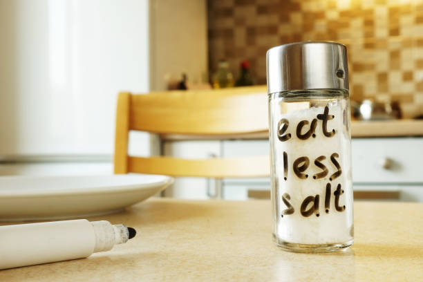 eat less salt handwritten on glass container. - sodium stock pictures, royalty-free photos & images