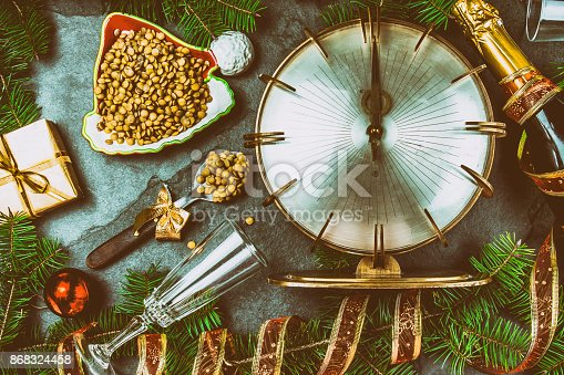 istock NEW YEARS EVE RITUAL. Eat spoon of lentil at midnigth. Holidey composition with vintage clock, lentil and Christmas decorations 868324458