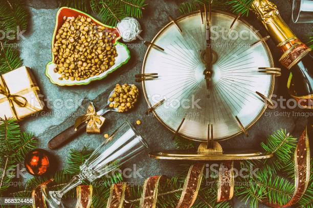 NEW YEARS EVE RITUAL. Eat spoon of lentil at midnigth. Holidey composition with vintage clock, lentil and Christmas decorations