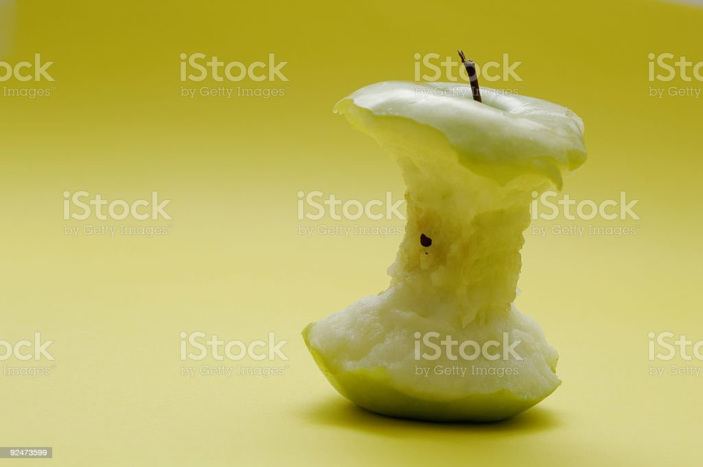 eaten green apple core against yellow royalty-free stock photo