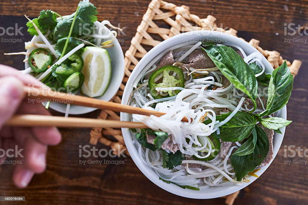 eating a bowl of pho with chopsticks stock photo